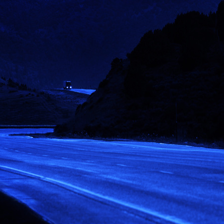 Truck driving at night along a curvy hilly road on hill side photo