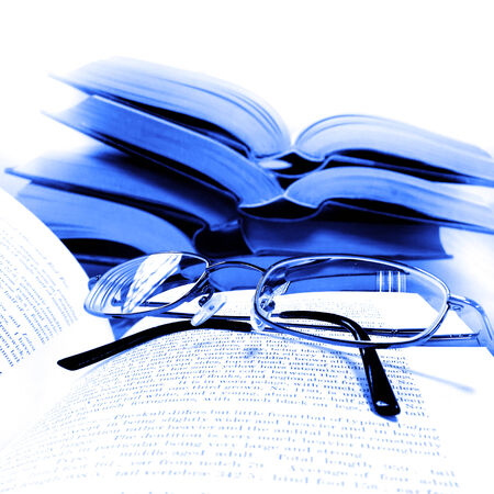 Stack of old books on a desk or table in a library with reading glasses