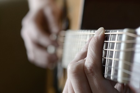 frets: Playing guitar strings and frets for making music