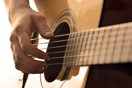making music: Playing guitar strings and frets for making music