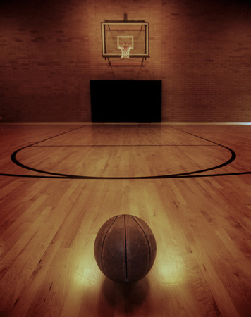 Basketball on floor of empty basketball court 스톡 콘텐츠