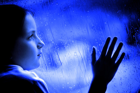 Girl looking out window on rainy day sad depressed feeling lonely