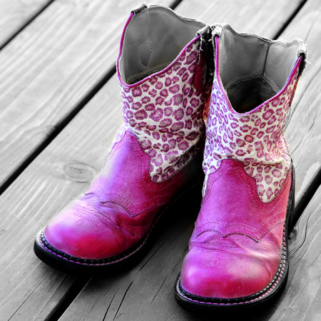 scuff: Detail of pink cowgirl cowboy boots on wood deck for a girl