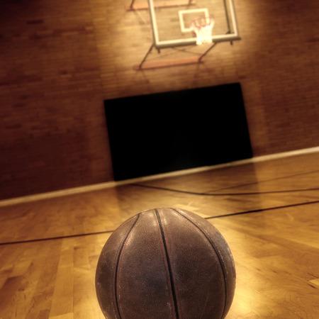 Basketball on floor of empty basketball court Foto de archivo