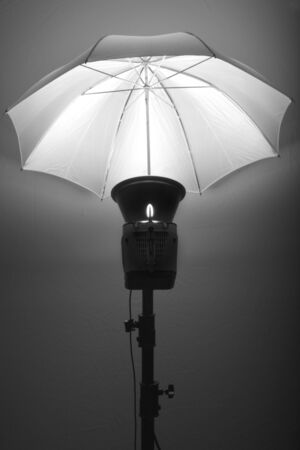 Detail of studio flash strobe light and umbrella on stand