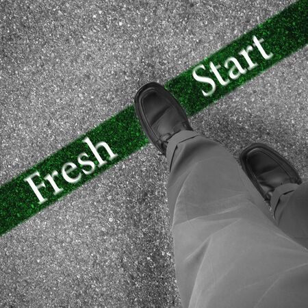 fresh start: Man walking across a green line with words fresh start Stock Photo