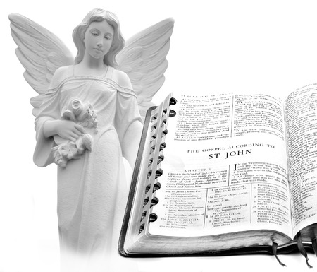 book of revelation: Open pages of bible isolated on white background with Angel Stock Photo