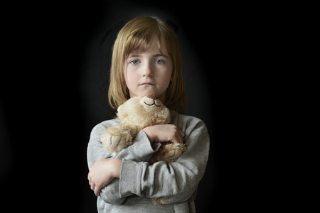 stuffed animals: Young little girl holding hugging teddy bear Stock Photo
