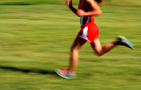 Runner wearing red running a race with fast motion photo