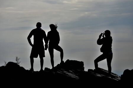 deatil: Deatil of couple hiking on rocks with friend taking picture