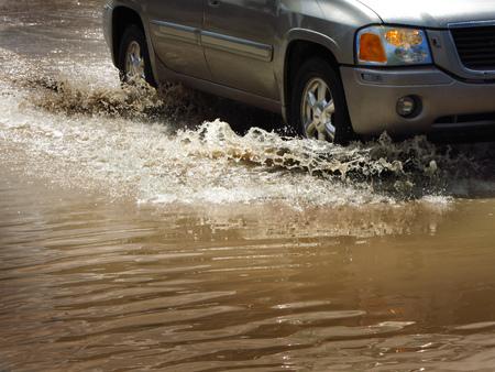 Detail of car driving through flood waters splashing