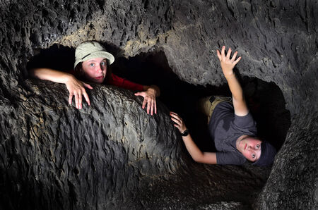 cave exploring: View of two kids exploring inside cave rocks