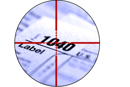 figuring: Detail closeup of current tax forms for IRS filing with crosshairs to destroy taxes Stock Photo