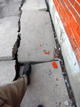 Man walking on broken dangerous cracked sidewalk and brick wall