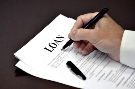 documentos: Documento de pr�stamo y el acuerdo con la pluma y la firma de la mano Foto de archivo