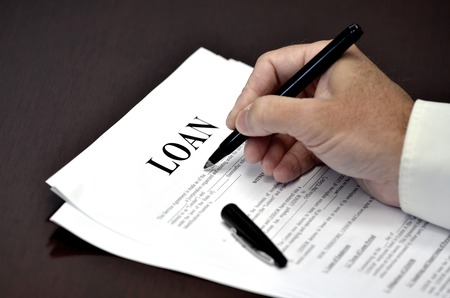 commercial sign: Loan document and agreement with pen and hand signing