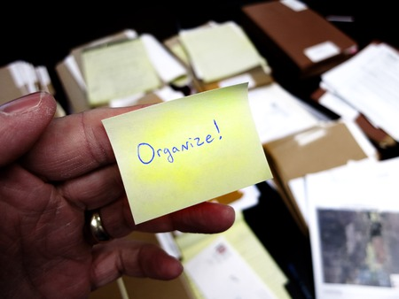 messy: Messy office with hand holding note saying Get Organized