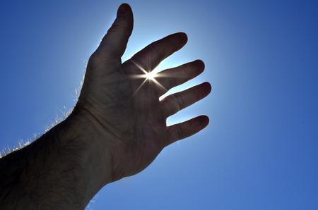 upward struggle: Persons hand reaching in hope towards heaven with sunlight shining through