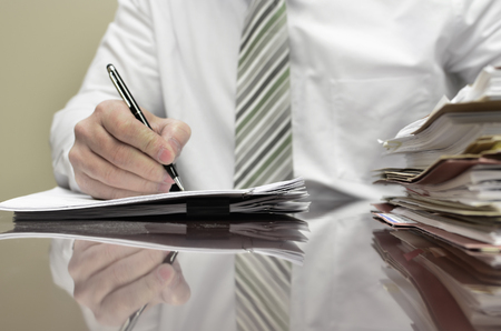 Businessman sitting at desk with pad of paper and piles fileswriting photo
