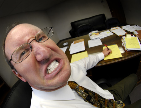 harassing: Mean looking man in business office gritting teeth Stock Photo