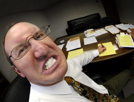 Mean looking man in business office gritting teeth Foto de archivo