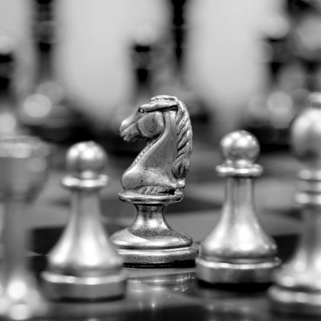 chessmen: Chess board with white knight facing opponent in match