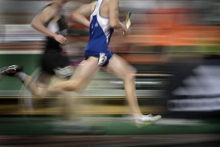 carrera de relevos: Corredor que corre una carrera alrededor de una pista con las líneas que sostienen relé batuta