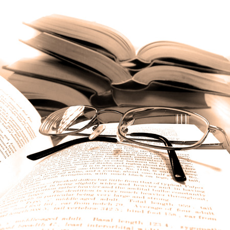 studious: Stack of old books on a desk or table in a library with reading glasses