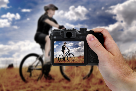 taking photograph: Hand holding digital camera taking photograph of woman riding mountain bike