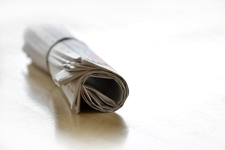topicality: Detail of rolled up newspaper on desk or table with rubber band