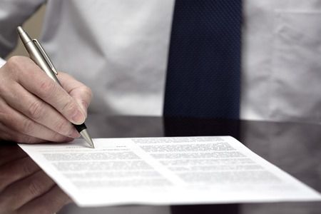 Man signing contract or agreement paper with pen wearing white shirt and tie photo