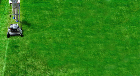 mowing grass: Young Girl Mowing green grass lawn with push mower