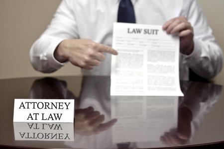 law suit: Attorney at Law sitting at desk holding Lawsuit suit