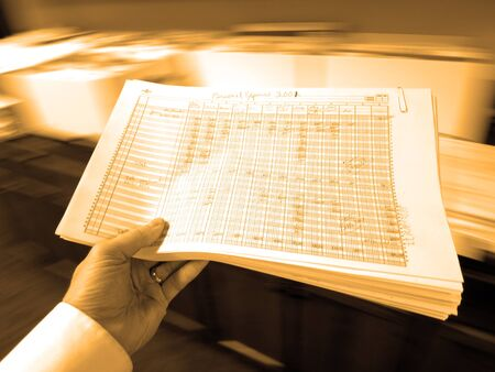 spreadsheets: Businessman in office holding packet of documents spreadsheets