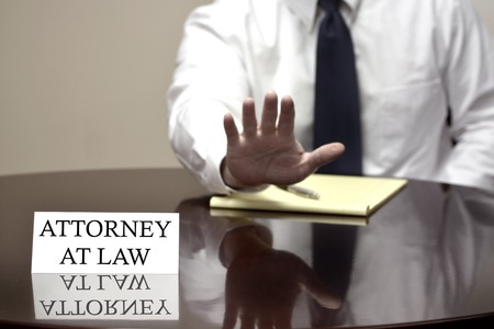 litigate: Attorney at Law sitting at desk with hand up to stop deal or talking negotiation Stock Photo