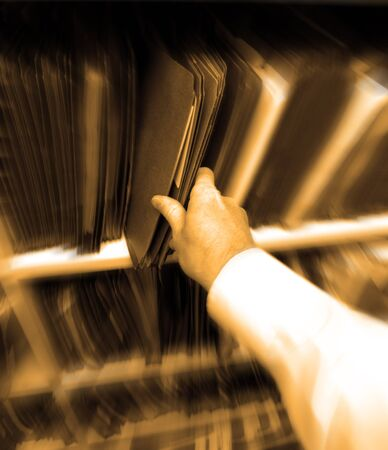 folder with documents: Businessman in office pulling file folder of documents off shelf
