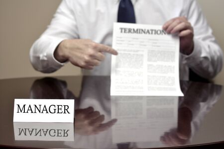 financial official: Manager sitting at desk holding Termination document Stock Photo
