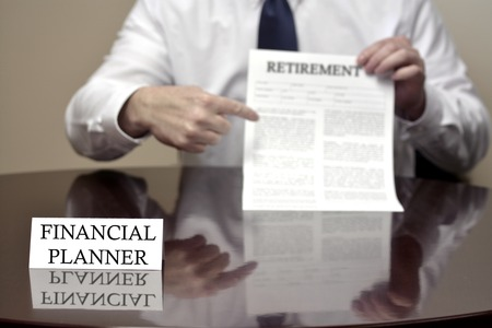 financial planner: Financial Planner sitting at desk holding Retirement document Stock Photo