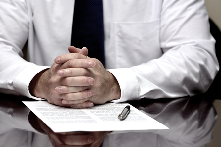 Man with contract or agreement paper with pen wearing white shirt and tie photo