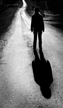 Girl walking on bright road black and white with shadow Stok Fotoğraf
