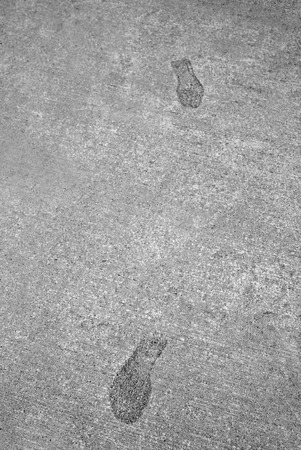 imprint: Detail of footsteps or footprints frozen in hard concrete cement