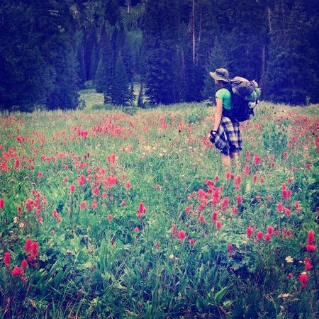 fiori di campo: Donna giovane backpacking in fiori Archivio Fotografico