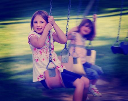niñas jugando: Niñas jugando en columpio en un parque