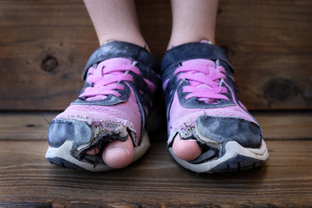 Detailed photo of shoes with holes in them and toes sticking out child kid young Stock Photo - 41457299