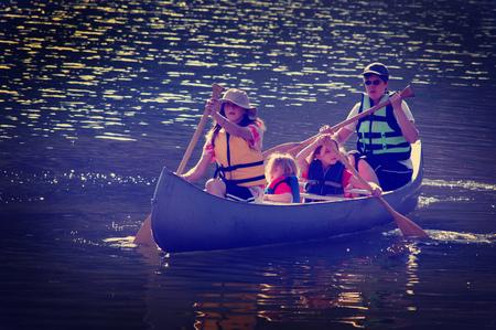 canoa: familia en una canoa en un lago en el verano Foto de archivo