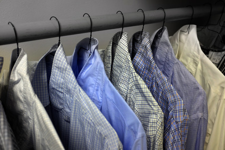 Row of dress shirts hanging on hangers in closet choice of clothing Stockfoto