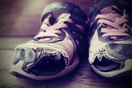 athletic wear: Old shoes with holes worn down shabby for homeless clothing
