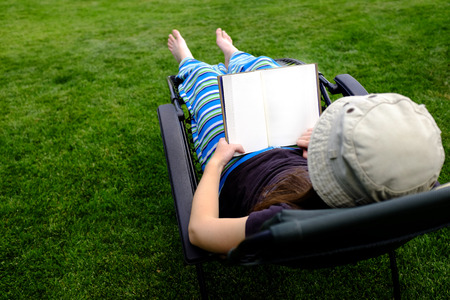 seating: Photo of Person Lounging in Lawn Chair Relaxing and Reading Book