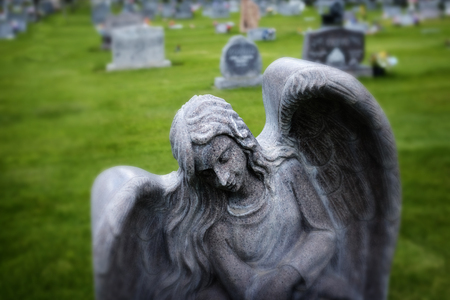 angel headstone: Detail of angel headstone in graveyard with green grass Stock Photo