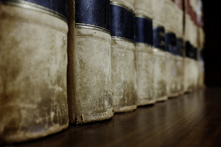 book concept: Long row of old leather law books on a shelf